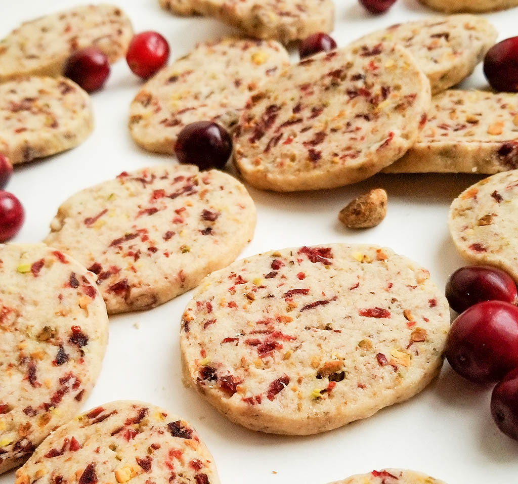 round ginger shortbread cookie with bits of dried cranberries and pistachios on white surface