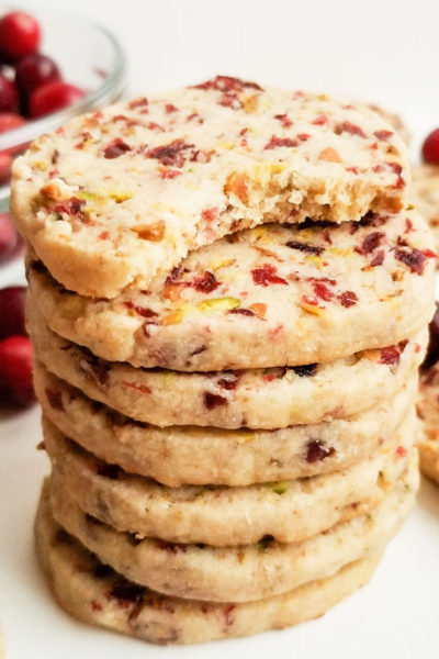 round ginger shortbread cookie with bits of dried cranberries and pistachios stacked on white surface