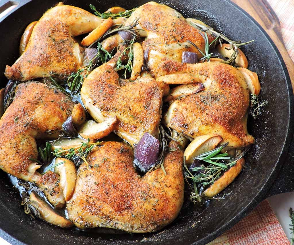roasted leg quarter chicken with apple slices purple onions and herbs in black cast iron skillet