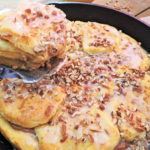 biscuits in black cast iron skillet stuffed with sweet potato pie filling and topped with white glaze and pecans
