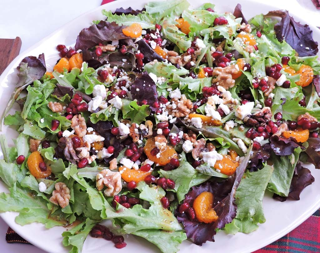 holiday spring mix salad with oranges pomegranate seed walnuts and feta on a white plate