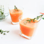 orange drink made with persimmon, carrot, thyme, lemon, honey; in a glass with thyme sprig on top on white surface