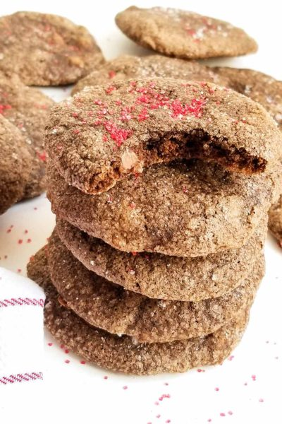 spiced double chocolate chip cookies stacked with red sprinkles on a white surface