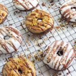 chocolate donuts iced with white chocolate and peanut butter, drizzled with milk chocolate, topped with almonds and pistachios on a wire rack
