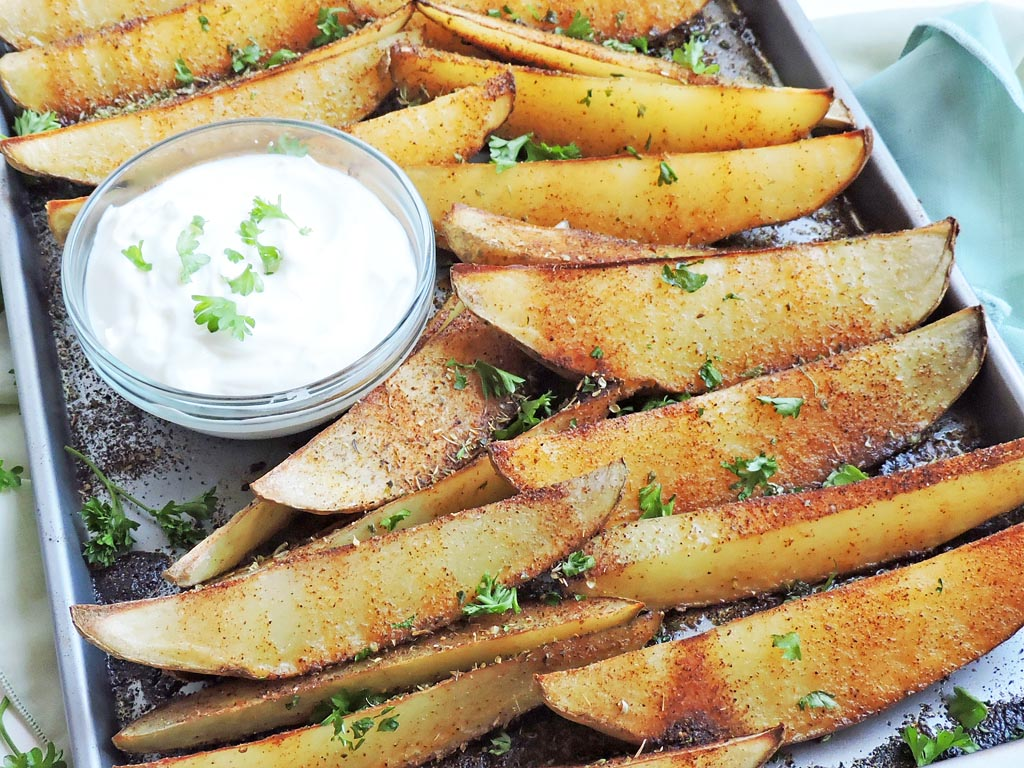 roasted potato wedges, seasoned with chili powder, on a baking sheet sprinkled with parsley with a bowl of greek yogurt/sour cream on the side