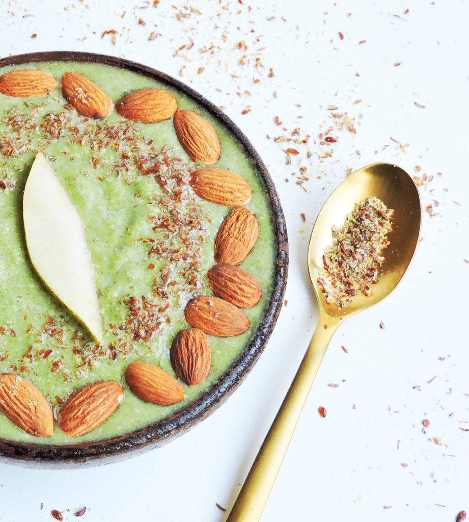 Green vegan smoothie in wooden bowl topped with almonds, flax seed meal, and a slice of pear on a white surface, gold spoon on the side