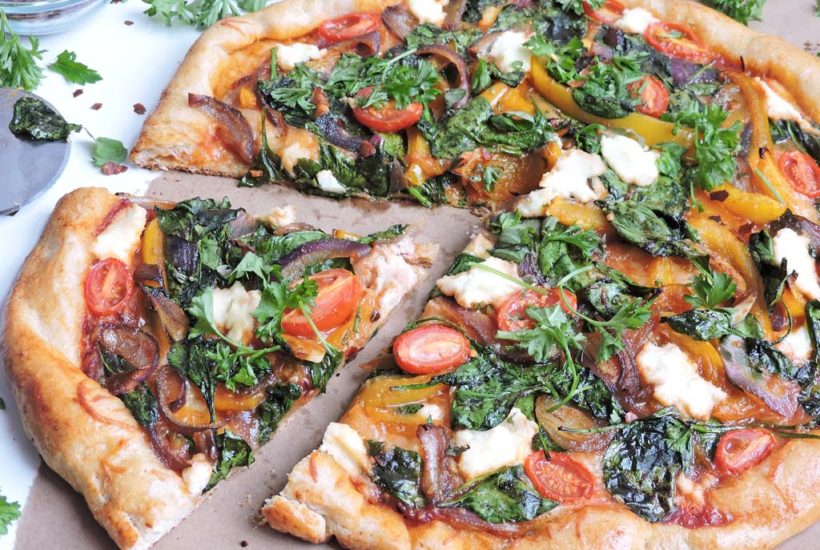 Sliced gourmet style veggie pizza topped with spinach, yellow bell pepper, purple onions, garlic, slice grape tomatoes, and ricotta cheese, on a piece of brown paper on a white surface