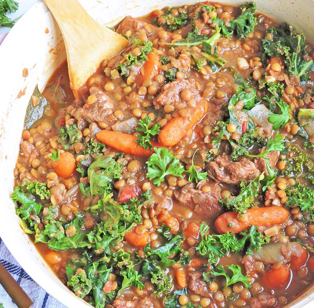 Kale, Lentil, and Beef Stew with carrots and parsley on top, in a pot with a wooden spoon