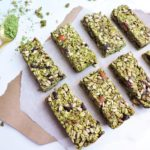 granola bars made with matcha green tea powder, almonds, sunflower seeds, dried cranberries, on a brown and white surface