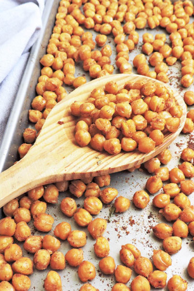 Simple Crunchy Roasted Garlic Chickpeas on a baking sheet with a wooden spoon