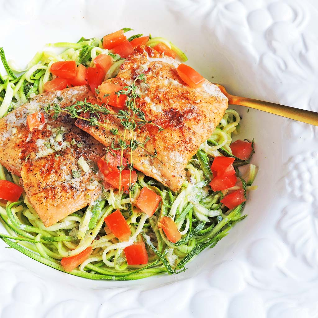 grilled salmon with red diced tomatoes and thyme on top of green zucchini noodles, in a white bowl