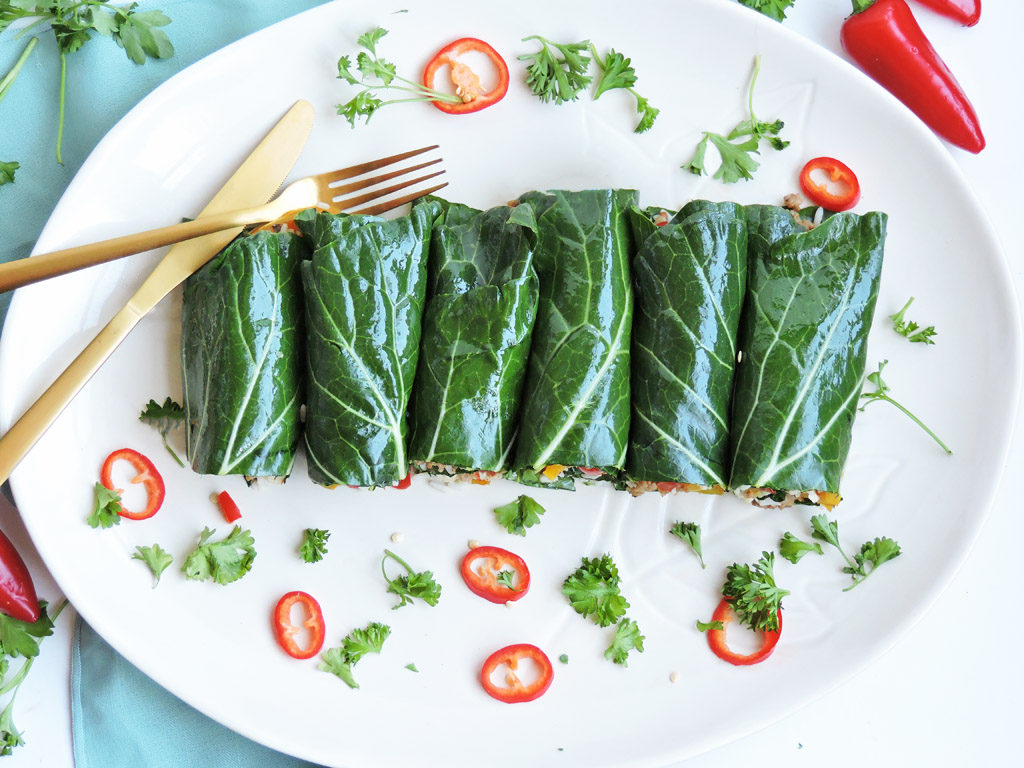 Turkey Sausage Stuffed Collard Green Wraps with rice and yellow and red bell peppers, on a white plate with slice red peppers