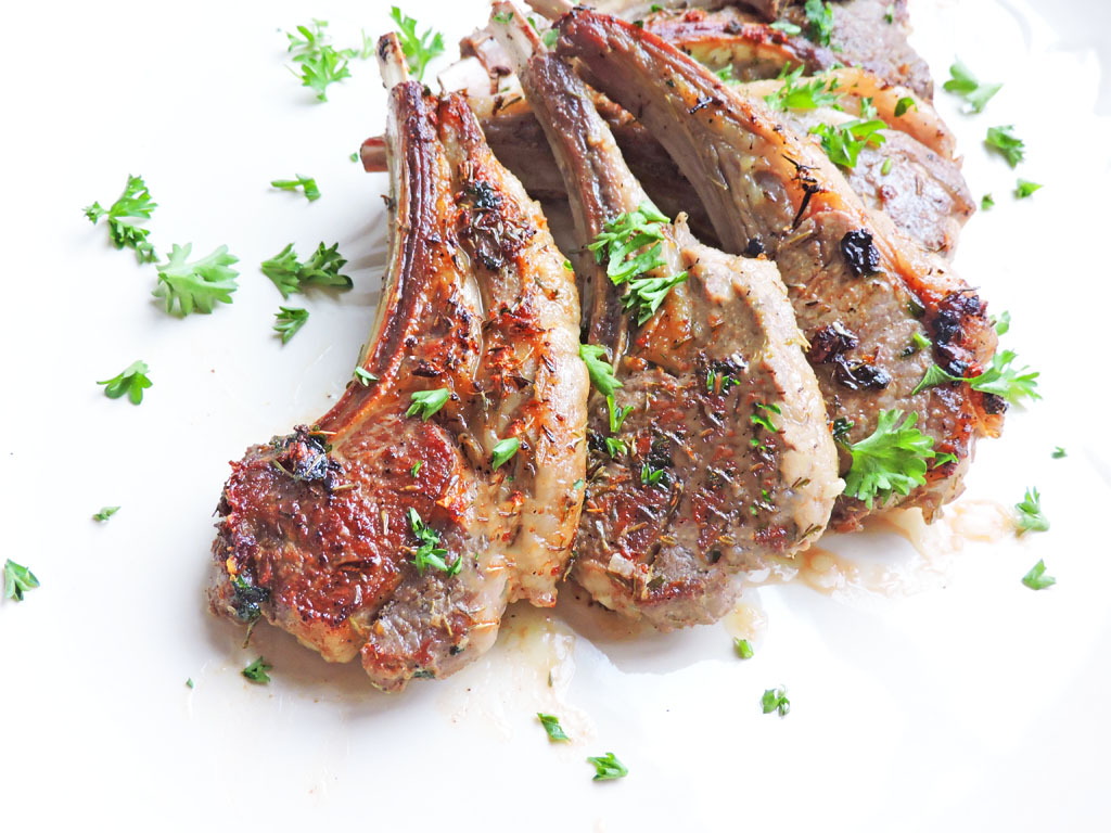 Date Night Herb Crusted Lamb Chops, sprinkled with parsley on a white plate. perfect for Valentine's Day