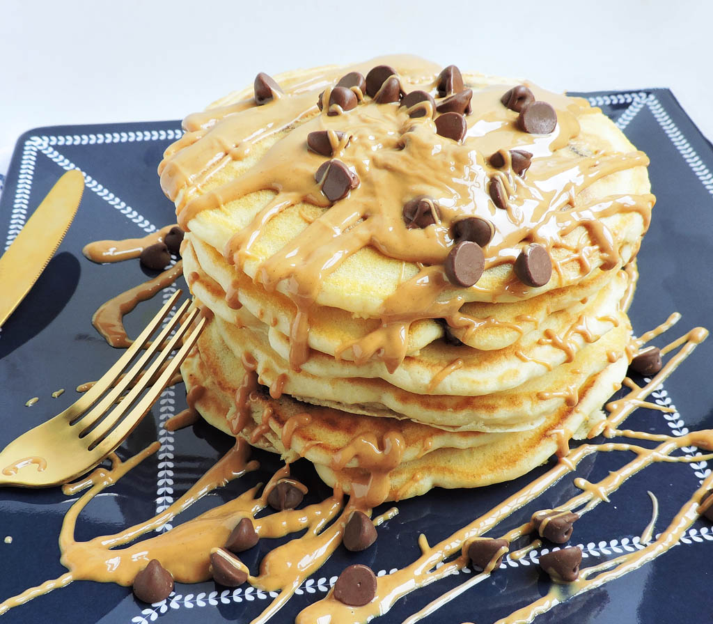 Extra Fluffy Chocolate Chip Pancakes stacked and topped with a peanut butter drizzle and chocolate chips, on a navy blue plate, with gold utensils