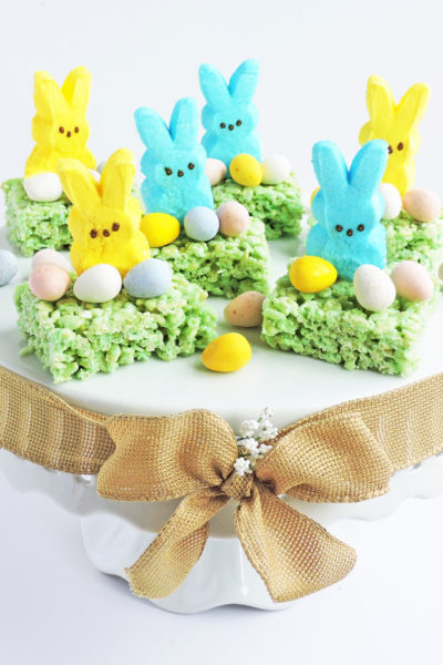 green rice cereal treats topped with yellow and blue marshmallow bunnies and candy eggs, sitting on a white pedastal for Easter