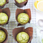 Light and Fluffy Matcha Lemon Muffins, green muffins in brown muffin liners on a wire rack next to lemons and measuring spoons. St. Patrick's Day
