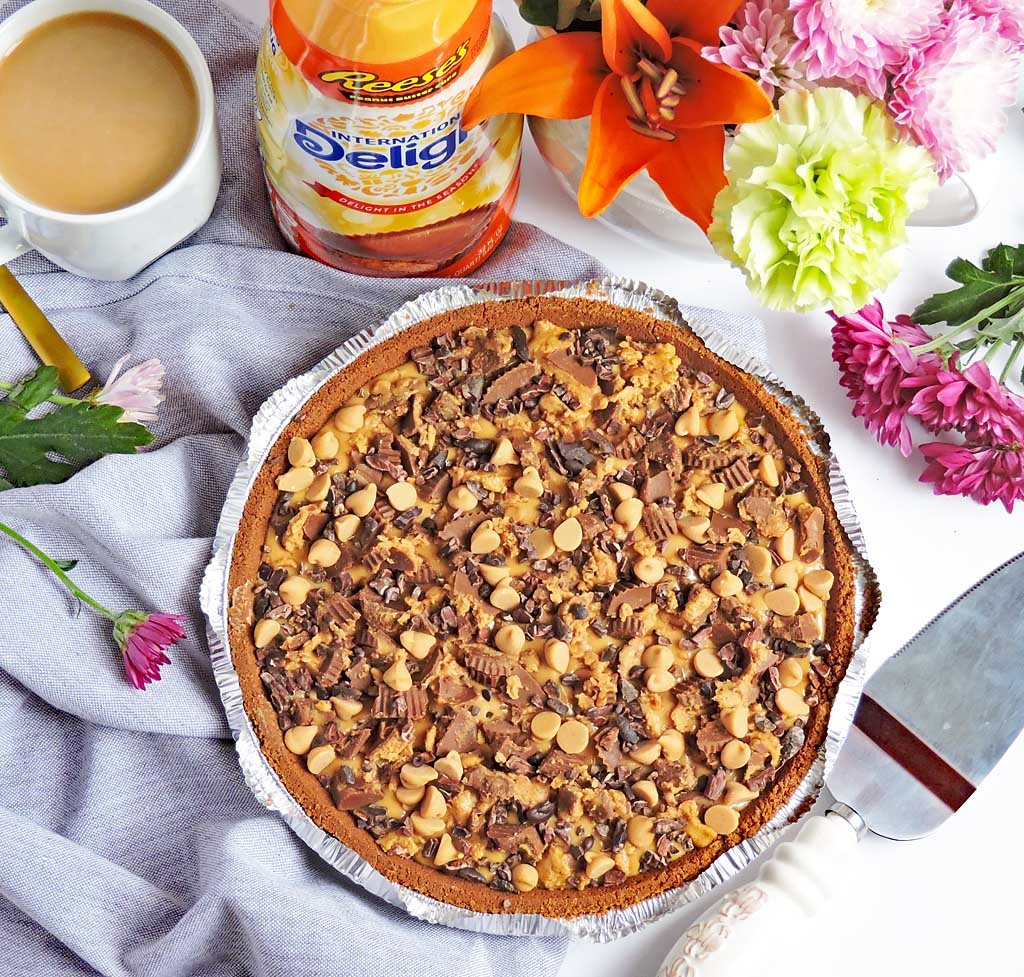 No-Bake Greek Yogurt Peanut Butter Pie, with crushed Reese's cup candy on top, placed next to a bottle of International Delight Creamer Reese's Cup, coffee and Spring flowers