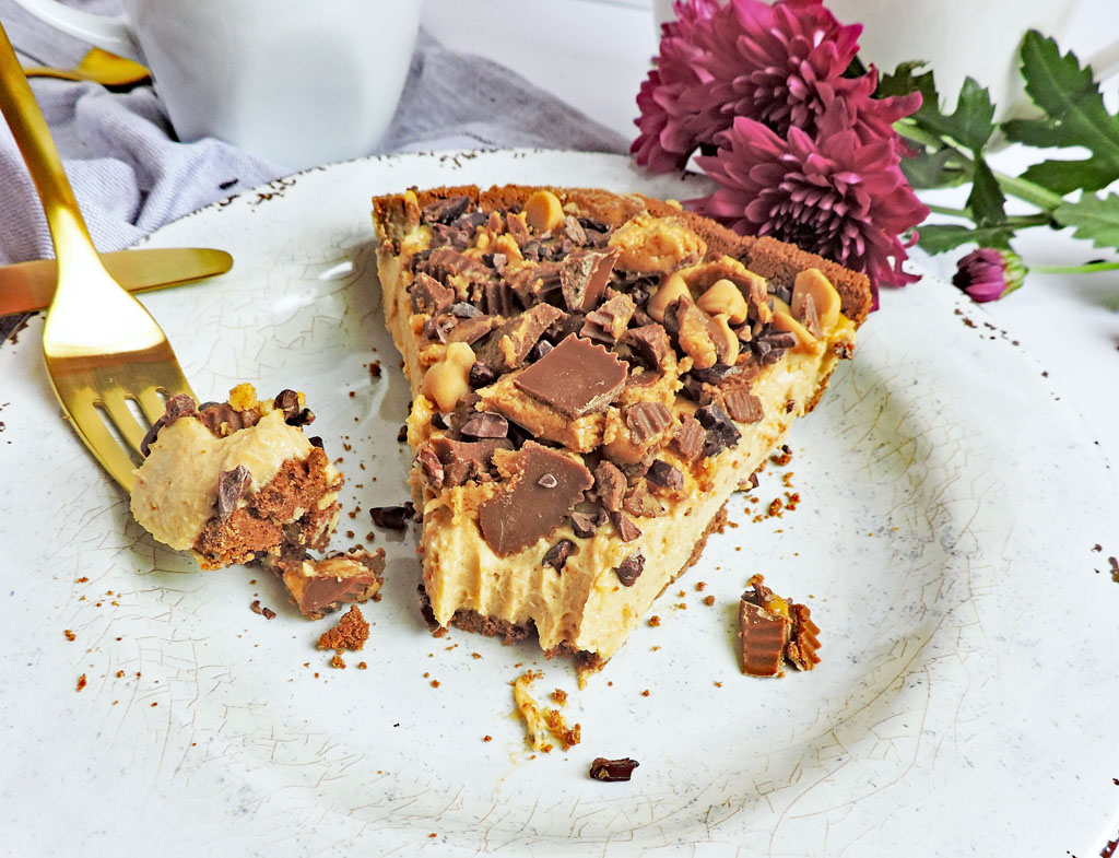 No-Bake Greek Yogurt Peanut Butter Pie, with crushed Reese's cup candy on top, sliced with a gold fork next to slice pie, placed next to a bottle of International Delight Creamer Reese's Cup, coffee and Spring flowers