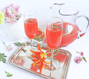 Rosemary Infused Grapefruit Mimosa, for brunch, served in champagne flutes on a silver tray with fresh rosemary sprigs inside of glasses and Spring flowers in the background