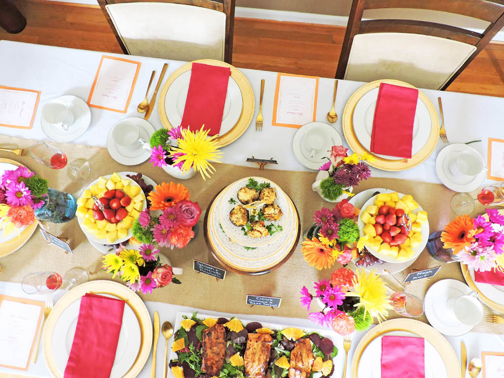 spring or mother's day brunch table setting with white tablecloth, burlap table runner with bright pink and yellow spring flowers. pink napkins and gold utensils