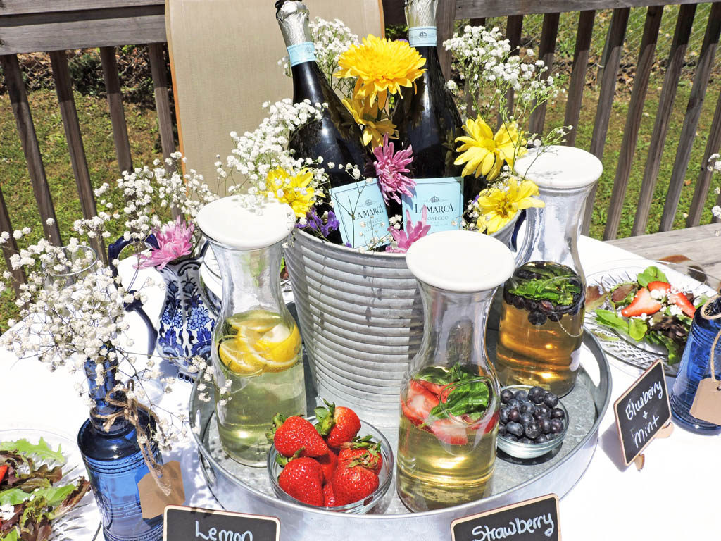 DIY Rustic Garden Party Centerpiece + Cocktail Station featuring 2 bottles of La Marca Prosecco in a tin bucket with flowers on a tin tray