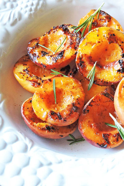 Spiced Grilled Peaches with rosemary on top served in a white bowl