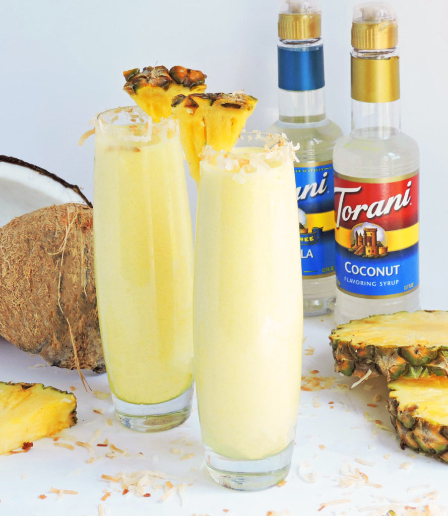 Tropical Pineapple Coconut Cooler served in a tall glass with toasted coconut around the rim, and pineapple wedge-made with Torani Syrups