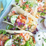 Cajun Shrimp and Fish Tacos. Tortillas filled with shrimp and fish, guacamole, lime, tomatoes, red cabbage, sour cream. served on a white wooden tray