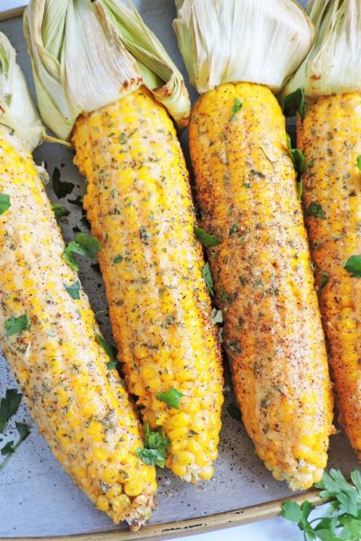 Lightened Up Spicy Mexican Street Corn with the husks on a silver plate, with parsley sprinkled on top