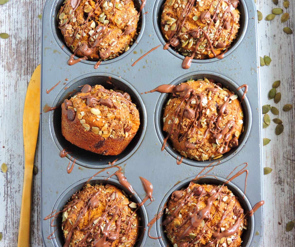 Chocolate Pumpkin Streusel Muffins in a tin muffin pan with a chocolate drizzle. beautifuleatsandthings.com