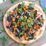 Garlicky Kale Sausage Butternut Squash Pizza-made with turkey italian sausage on a wooden board, garnished with parsley