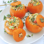 Mini Sausage & Rice Stuffed Pumpkins served on a white plate with thyme on top, the perfect Fall recipe for Thanksgiving