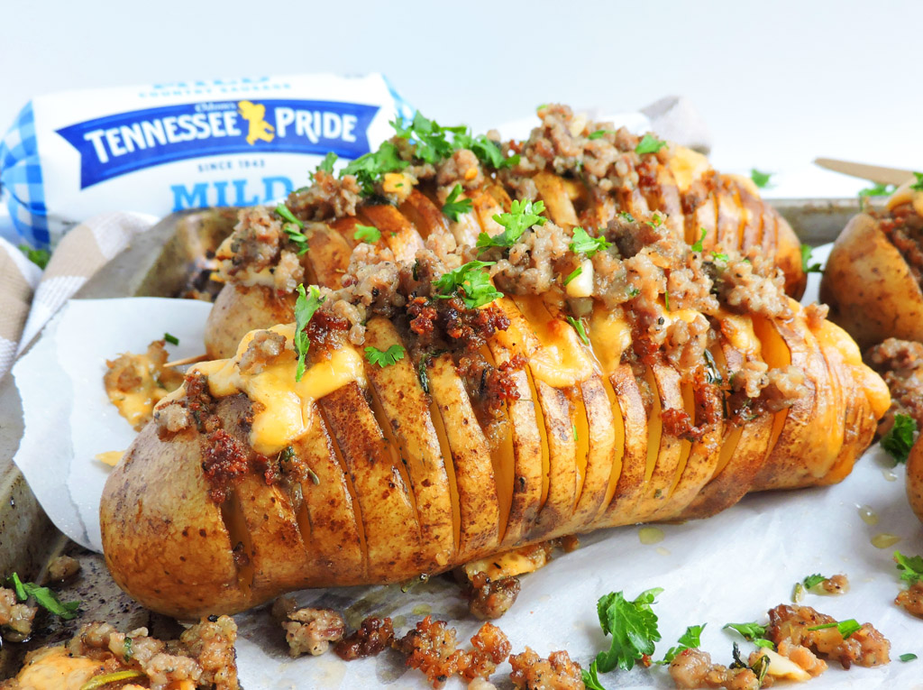 Spicy Smoked Gouda & Sausage Hasselback Potatoes made with Odom's Tennessee Pride Mild Sausage, topped with rosemary and parsley
