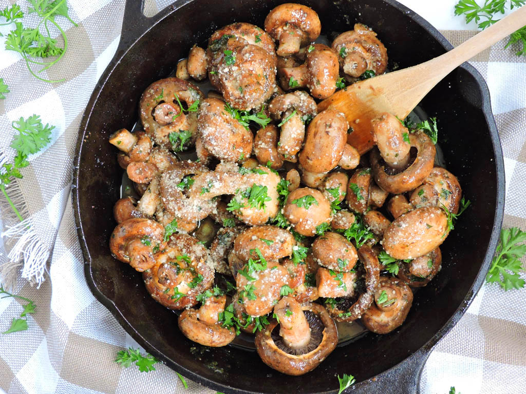 Ranch Garlic Parmesan Sauteed Mushrooms in a black cast iron skillet, with parsley on top and a wooden spoon