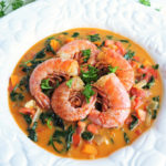 Ndole, a Cameroonian Peanut Stew served in a white bowl with cajun shrimp or prawns on top