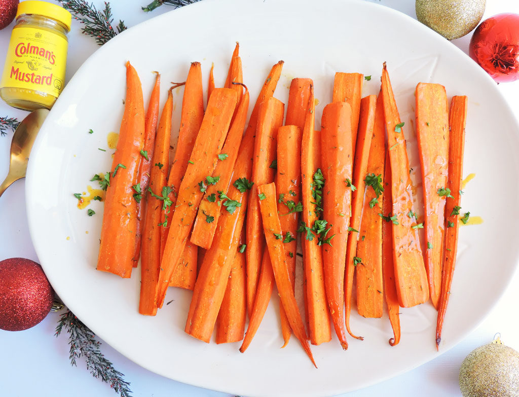 Ginger Maple Mustard & Herb Roasted Carrots with parsley on top made with Colman's Mustard on a white plate