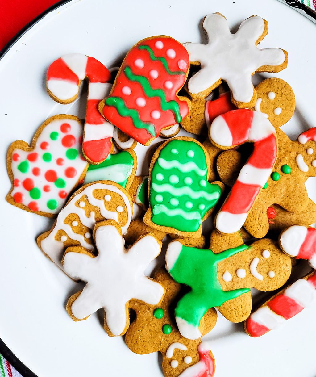 decorated gingerbread cookies with Christmas colors, red and green, on a white plate, decorated with vegan royal icing. Beautifuleatsandthings.com