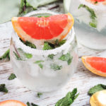 Fresh Mint & Grapefruit Spritzer made with sparkling grapefruit mineral water, in a stemless wine glass and a wedge of grapefruit on top