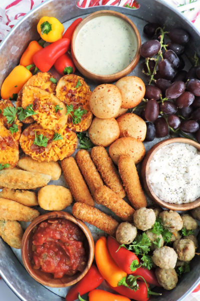 How to Create the Perfect Game Day Spread in Less Than 30 Minutes-FarmRich Mozzarella Stick, Jalapeno Peppers, Loaded Potato Skins, Meatballs, served with vegetables and fruit for game day