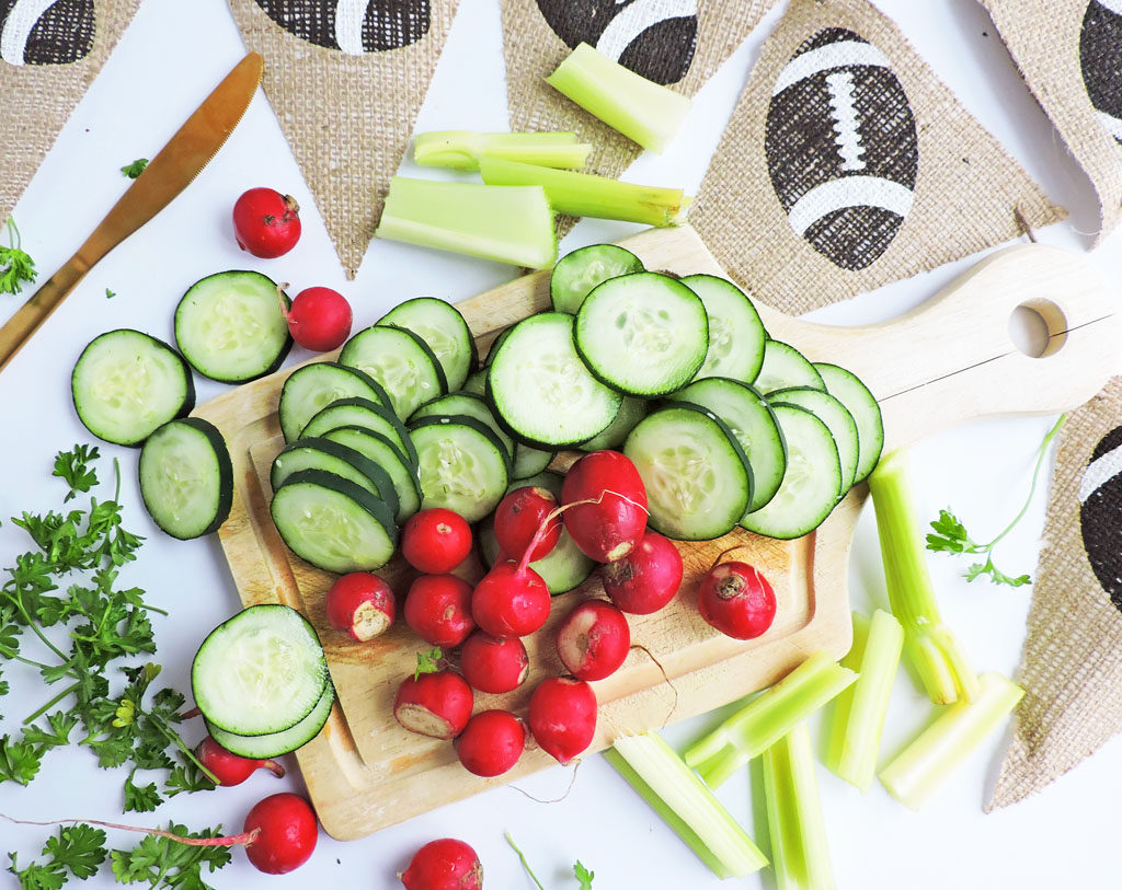Sliced cucumbers, radishes, celery on a cutting board with a burlap football banner-Easy Mini Game Day Snack Baskets