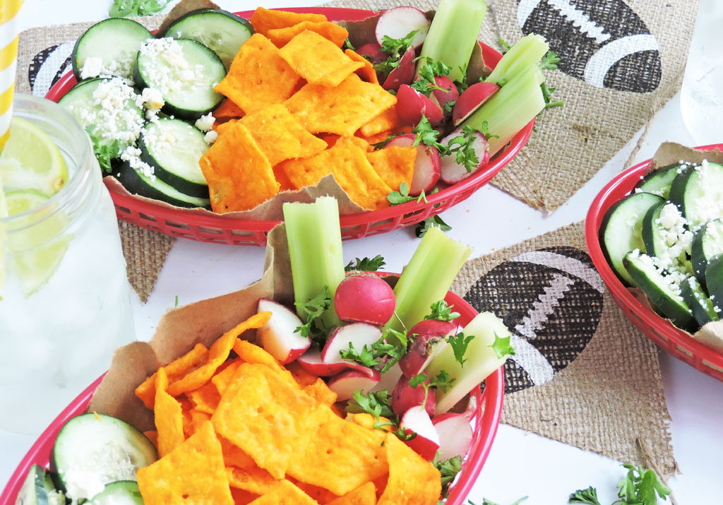 Red french fry baskets filled with sliced cucumbers, radishes, celery, and Cheez-It Snap'd crackers on a white surface with a football banner for game day-Easy Mini Game Day Snack Baskets