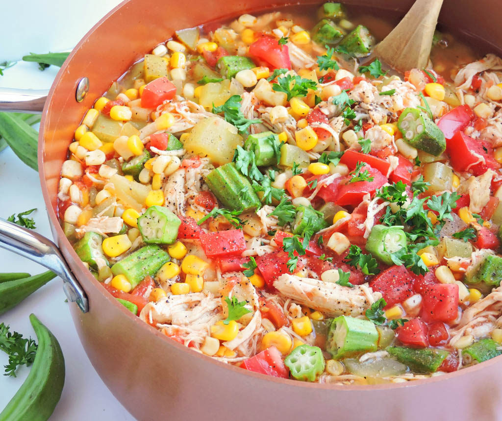 Okra, Corn, & Tomato Chicken Stew in a copper pot with a wooden spoon, topped with parsley