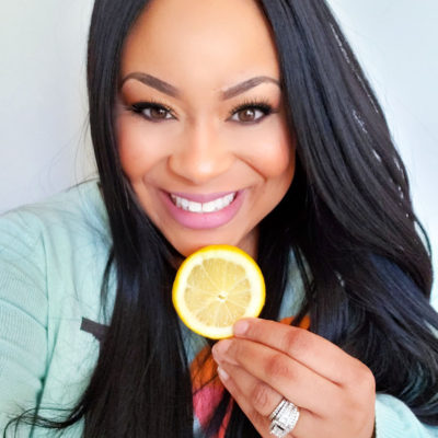 My Top 5 Beauty Products That Can Be Found In Your Kitchen- African American Woman Registered Dietitian smiling and holding a lemon