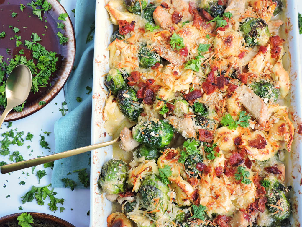 Cheesy Chicken & Brussels Sprouts Pasta Bake in a white casserole dish with brussels sprouts, chicken, Parmesan cheese, cheese tortellini, and bacon. gold spoon in casserole. www.beautifuleatsandthings.com