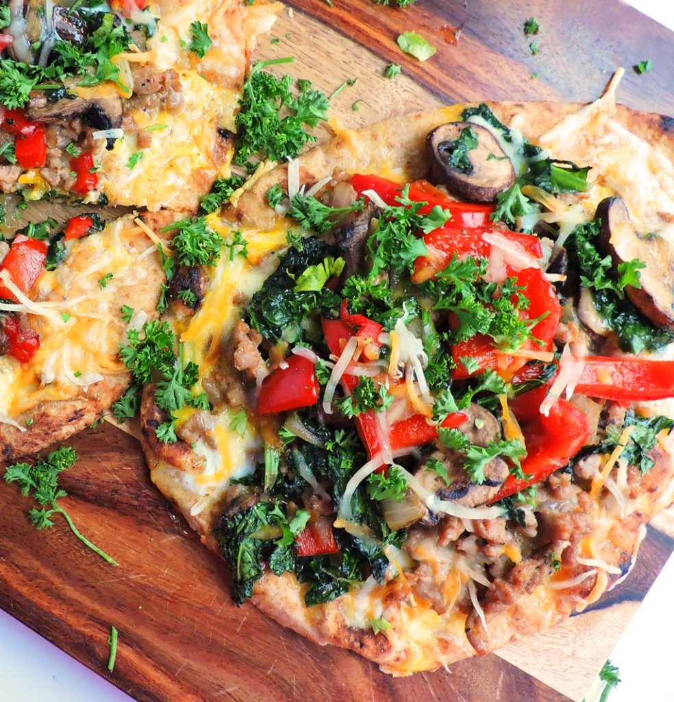 Whole Wheat Sausage & Veggie Flatbread Breakfast Pizza made with whole wheat naan topped with kale, red bell peppers, onion, mushrooms, turkey sausage, cheese, and eggs. beautifuleatsandthings.com
