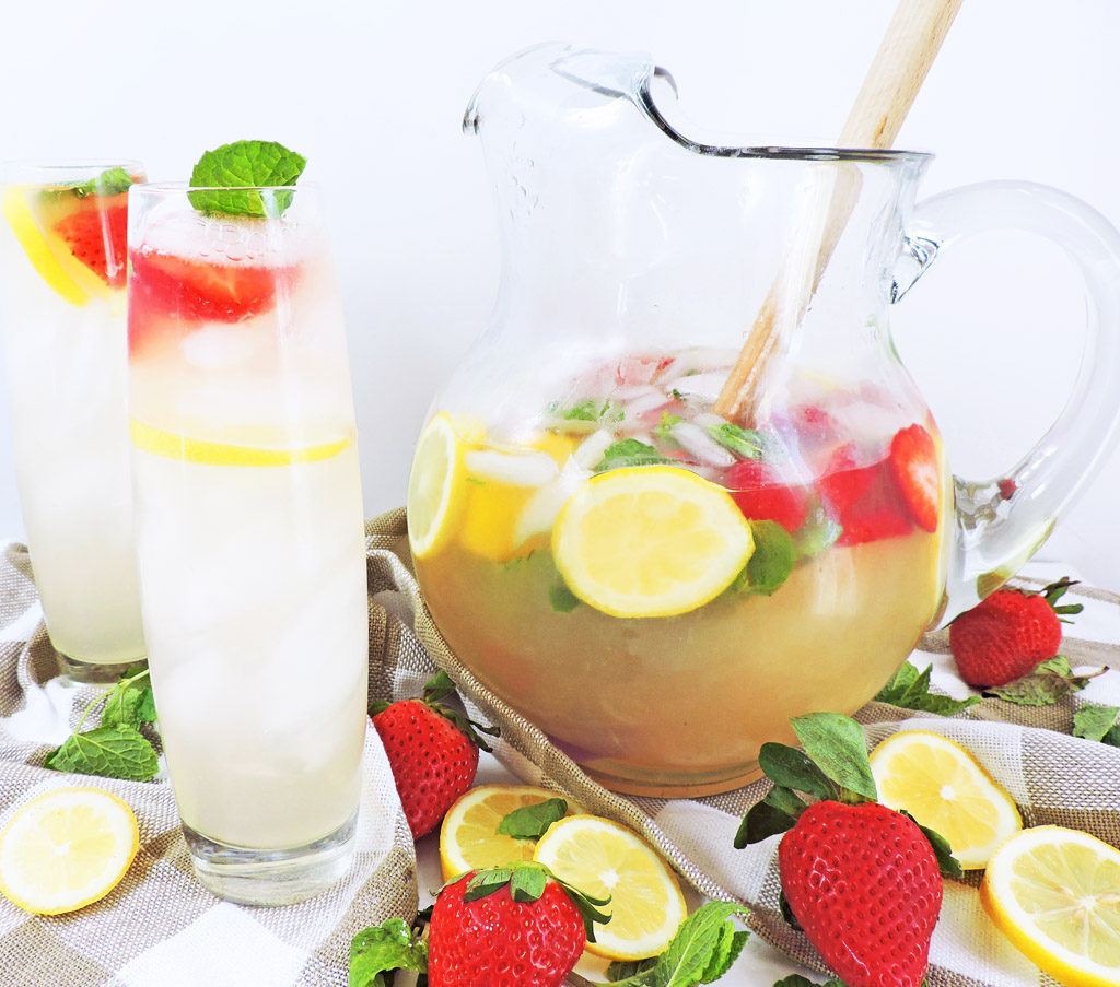 No Added Sugar Strawberry Mint Lemonade in a pitcher with sliced lemons, strawberries, and mint leaves on a white surface made with Splenda Naturals Stevia