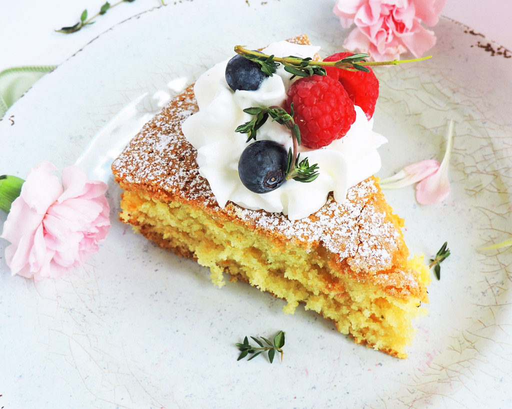 Rustic Lemon & Thyme Olive Oil Cake on a pink pedestal cake stand topped with raspberries, blueberries, lemon wedges, thyme, and powdered sugar, on a white surface with Spring pink flowers