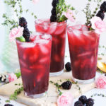 Peachy Blackberry & Thyme Cocktail served in a glass of ice topped with a pink flower, blackberry skewer, and fresh thyme. perfect for Spring, a bridal shower, wedding or mother's day