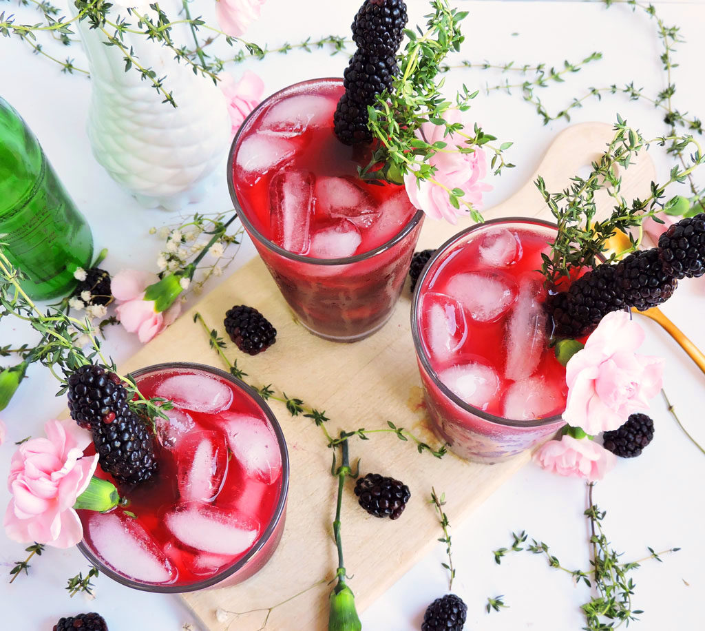 Peachy Blackberry & Thyme Cocktail served in a glass of ice topped with a pink flower, blackberry skewer, and fresh thyme. perfect for Spring, a bridal shower, wedding or mother's day beautifuleatsandthings.com