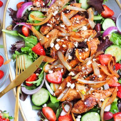 balsamic strawberry Greek chicken salad on a large platter with grilled chicken, sauteed onions, purple onions, cucumbers, strawberries, and feta cheese beautifuleatsandthings.com